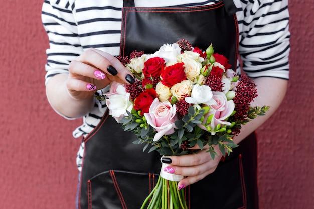Młoda Kwiaciarnia Trzyma ślubnego Bukiet Róże. Moda Nowoczesny Bukiet Różnych Kwiatów. Premium Zdjęcia