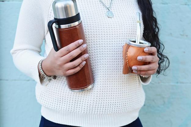 Młoda łacińska kobieta pije tradycyjnego yerba kolega herbaty. Premium Zdjęcia