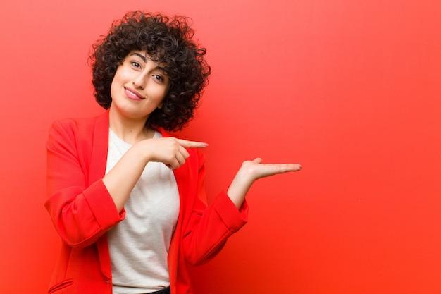 Młoda ładna afro kobieta uśmiecha się, czuje się szczęśliwa, beztroska i zadowolona Premium Zdjęcia