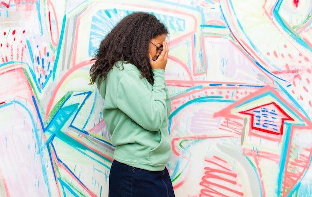 Młoda ładna Amerykanin Afrykańskiego Pochodzenia Kobieta Zakrywa Oczy Z Rękami Z Smutnym, Sfrustrowanym Spojrzeniem Rozpaczy, Płacze Przy Graffiti ścianie Premium Zdjęcia