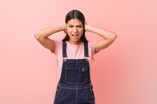 Młoda ładna arabska kobieta jest ubranym cajgu dungaree zakrywa ucho z rękami próbuje no słuchać zbyt głośnego dźwięka. Premium Zdjęcia