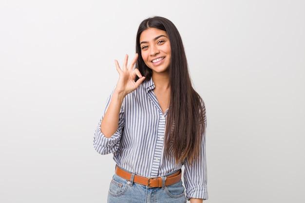 Młoda ładna arabska kobieta mruga okiem i trzyma w porządku gest ręką. Premium Zdjęcia