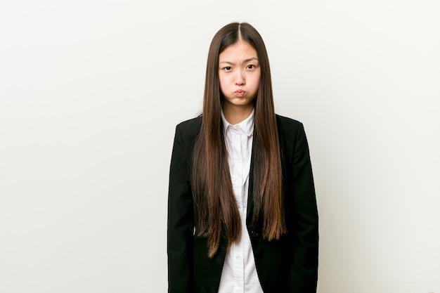 Młoda ładna chińska biznesowa kobieta dmucha policzki, ma zmęczonego wyrażenie. koncepcja wyrazu twarzy. Premium Zdjęcia
