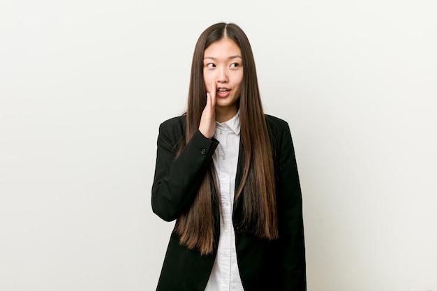 Młoda ładna Chińska Biznesowa Kobieta Mówi Tajną Gorącą Hamującą Wiadomość I Patrzeje Na Boku Premium Zdjęcia