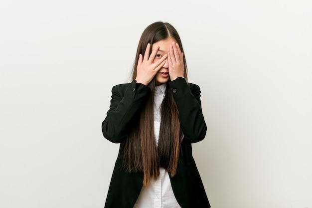 Młoda ładna Chińska Biznesowa Kobieta Mruga Palcami Przestraszonymi I Nerwowymi. Premium Zdjęcia