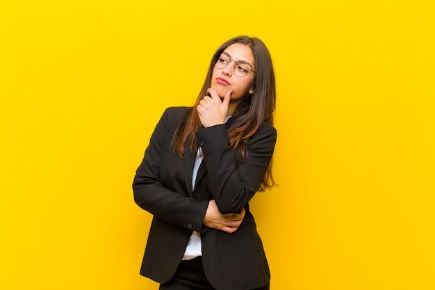 Młoda ładna kobieta czuje się zamyślona, zastanawia się lub wyobraża sobie pomysły, marzy i szuka do copyspace na pomarańczowej ścianie Premium Zdjęcia