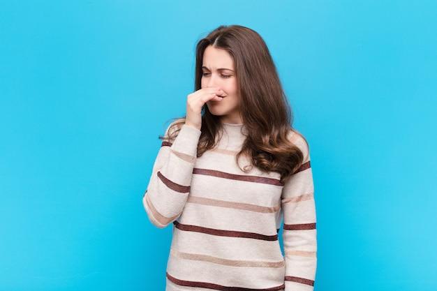 Młoda ładna Kobieta Czuje Się Zniesmaczona, Trzymając Nos, Aby Nie Poczuć Nieprzyjemnego I Nieprzyjemnego Smrodu Nad Niebieską ścianą Premium Zdjęcia
