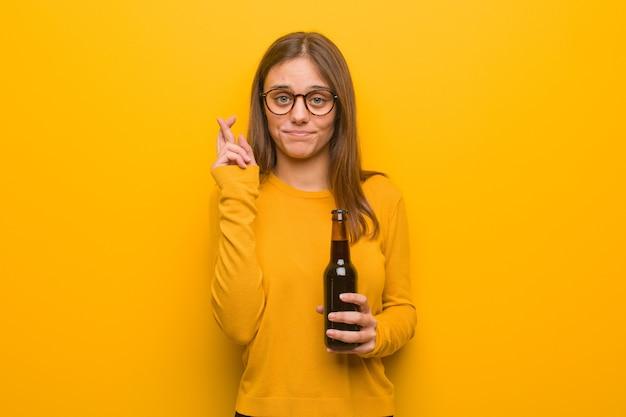 Młoda ładna Kobieta Kaukaski Kciuki Za Szczęście. Trzyma Piwo. Premium Zdjęcia
