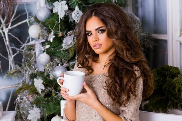 Młoda ładna Kobieta Marzy I Pije Kawę Lub Herbatę, Ciesząc Się Bożonarodzeniowym Porankiem, Portret Pięknej Damy W Ciepłych, Przytulnych Ubraniach Siedzącej Na Jasnym Tarasie Z Bliska Darmowe Zdjęcia