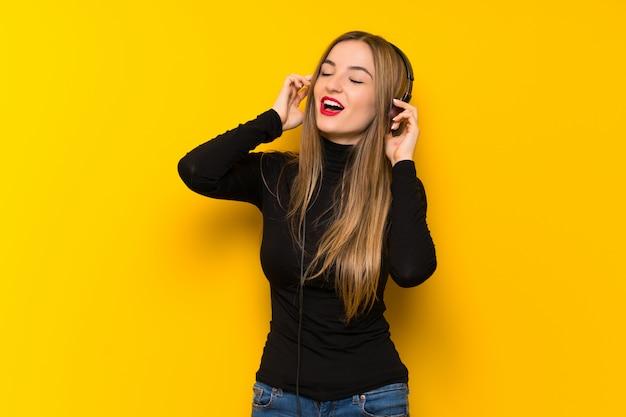 Młoda ładna Kobieta Nad żółtą ścianą, Słuchanie Muzyki W Słuchawkach Premium Zdjęcia