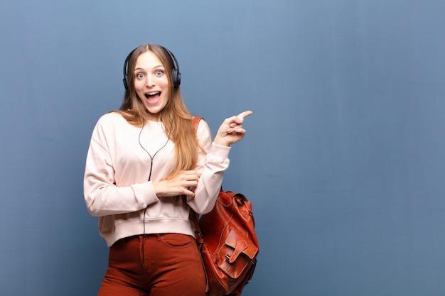 Młoda ładna Kobieta Przeciw Błękit ścianie Z Odbitkową Przestrzenią Premium Zdjęcia