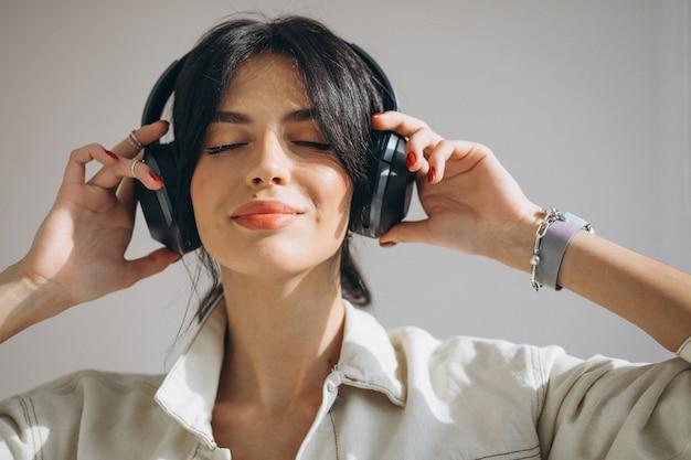 Młoda ładna Kobieta Słuchania Muzyki Na Słuchawki Bezprzewodowe Darmowe Zdjęcia