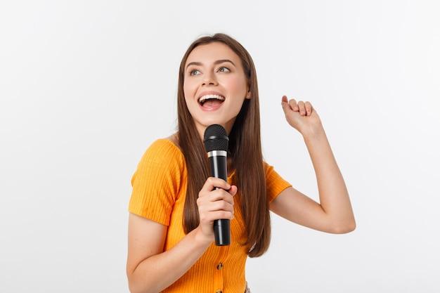 Młoda ładna kobieta szczęśliwa i zmotywowana, śpiewająca piosenkę z mikrofonem, przedstawiająca wydarzenie lub imprezę, ciesz się chwilą Premium Zdjęcia