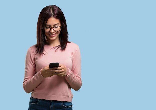 Młoda ładna kobieta szczęśliwa i zrelaksowana, dotykając telefonu komórkowego, korzystając z internetu i sieci społecznościowych Premium Zdjęcia