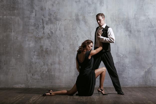 Młoda ładna Kobieta W Czarnej Sukni I Tango Tańca Człowieka Premium Zdjęcia