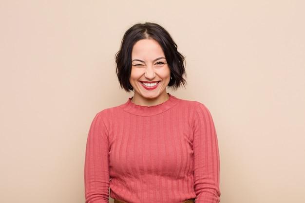 Młoda ładna Kobieta Wyglądająca Na Szczęśliwą I Przyjazną, Uśmiechnięta I Mrugająca Do Ciebie Okiem Z Pozytywnym Nastawieniem Premium Zdjęcia