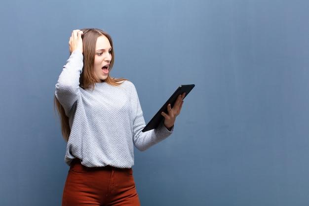 Młoda ładna kobieta z pastylki błękita ścianą z copyspace Premium Zdjęcia