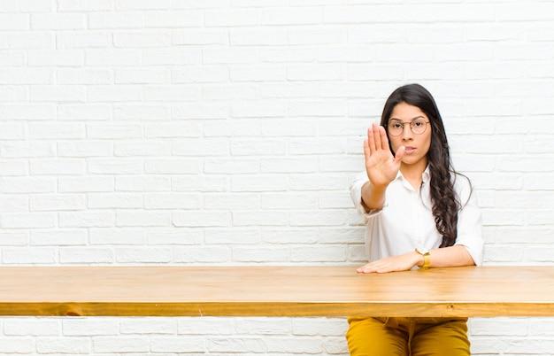Młoda ładna łacińska kobieta patrzeje poważnego, surowego, niezadowolonego i gniewnego pokazywać otwartą dłoń robi przerwie gestykulować obsiadanie przed stołem Premium Zdjęcia