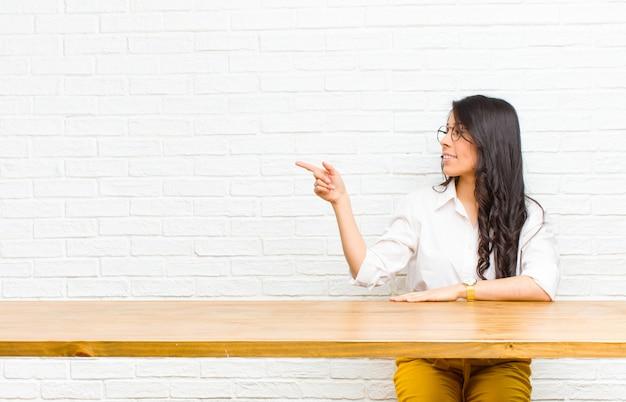 Młoda ładna łacińska kobieta stoi i wskazuje protestować na kopii przestrzeni, tylni widoku obsiadanie przed stołem Premium Zdjęcia
