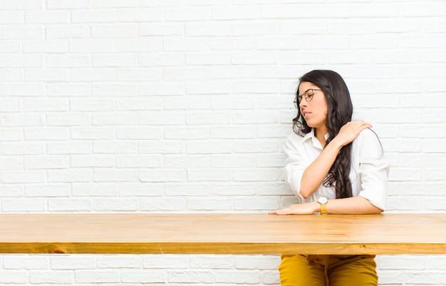 Młoda ładna latynoska czująca się zmęczona, zestresowana, niespokojna, sfrustrowana i przygnębiona, cierpiąca na bóle pleców lub szyi, siedząca przed stołem Premium Zdjęcia