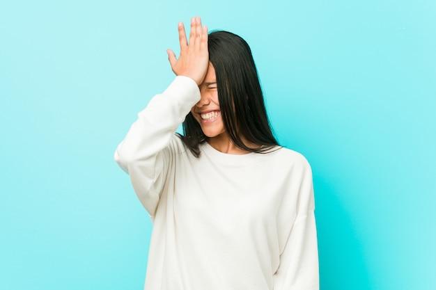 Młoda ładna latynoska kobieta zapominająca o czymś, uderzająca dłonią w czoło i zamykająca oczy. Premium Zdjęcia