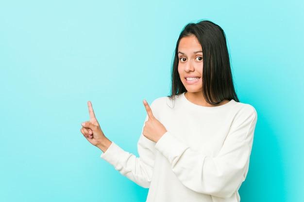Młoda ładna latynoska kobieta zszokował wskazujący palcami wskazującymi przestrzeń kopii. Premium Zdjęcia