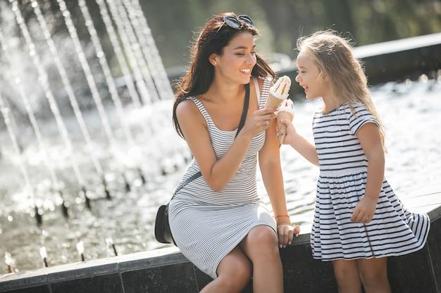 Młoda ładna Matka I Jej Córka Zabawy Razem Przy Fontannie. Piękna Kobieta I Jej Małe Dziecko Je Lody. Wesoła Rodzina Zabawy. Premium Zdjęcia