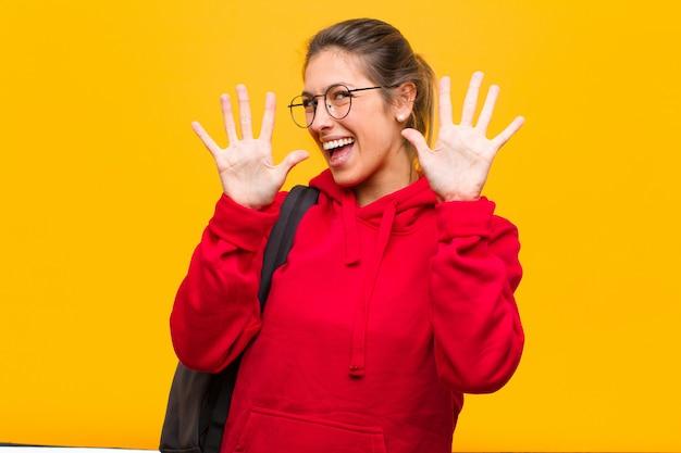 Młoda ładna studentka uśmiechnięta i wyglądająca przyjaźnie, pokazując numer piąty ręką do przodu, odliczając Premium Zdjęcia