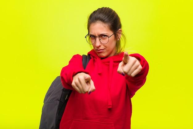 Młoda ładna Studentka Wskazująca Na Aparat Obiema Palcami I Z Gniewnym Wyrazem Twarzy, Nakazująca Ci Wypełnienie Obowiązku Premium Zdjęcia