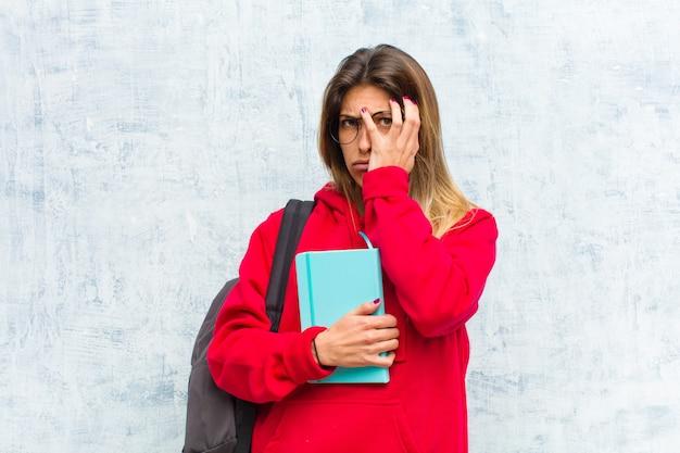 Młoda ładna studentka znudzona, sfrustrowana i senna po męczącym, nudnym i żmudnym zadaniu, trzymając twarz ręką Premium Zdjęcia