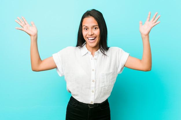 Młoda latynoska chłodna kobieta o niebieską ścianę, przyjmująca miłe zaskoczenie, podekscytowana i podnosząca ręce. Premium Zdjęcia