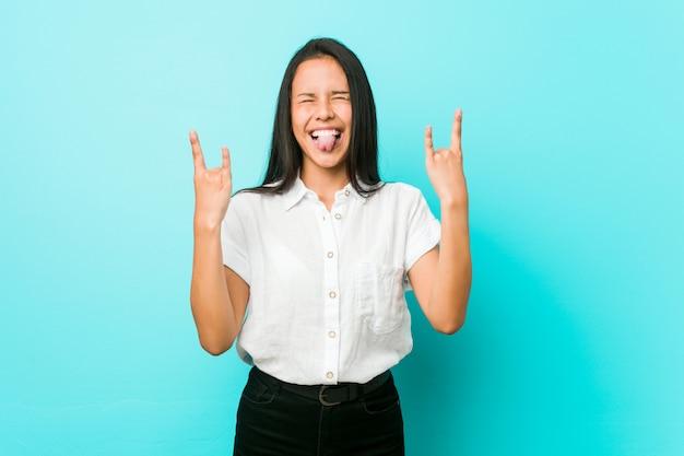 Młoda latynoska chłodno kobieta przeciw błękitnej ścianie pokazuje rockowego gest palcami Premium Zdjęcia