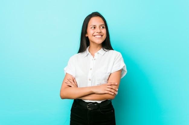 Młoda latynoska chłodno kobieta przy błękitnej ściany ono uśmiecha się ufny z skrzyżowanymi rękami. Premium Zdjęcia