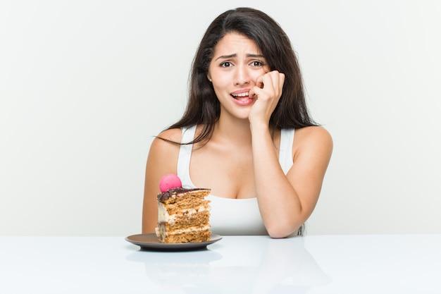 Młoda Latynoska Kobieta Je Ciasto Obgryzające Paznokcie, Nerwowa I Bardzo Niespokojna. Premium Zdjęcia