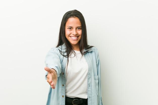 Młoda latynoska kobieta rozciąga rękę przy kamerą w powitanie gescie. Premium Zdjęcia