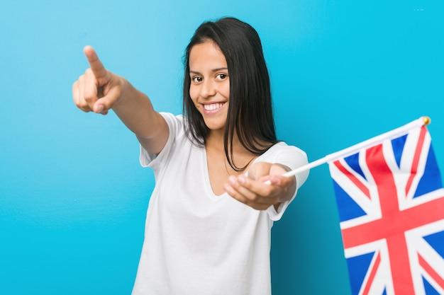 Młoda latynoska kobieta trzyma wesołej flagi królestwa wesoły uśmiecha się do przodu. Premium Zdjęcia