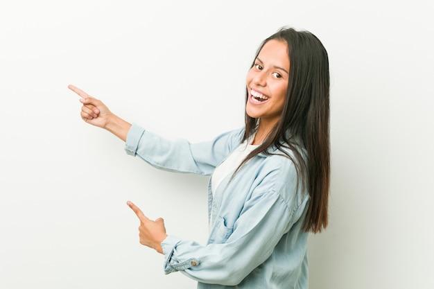 Młoda latynoska podekscytowana wskazując palcami z dala. Premium Zdjęcia