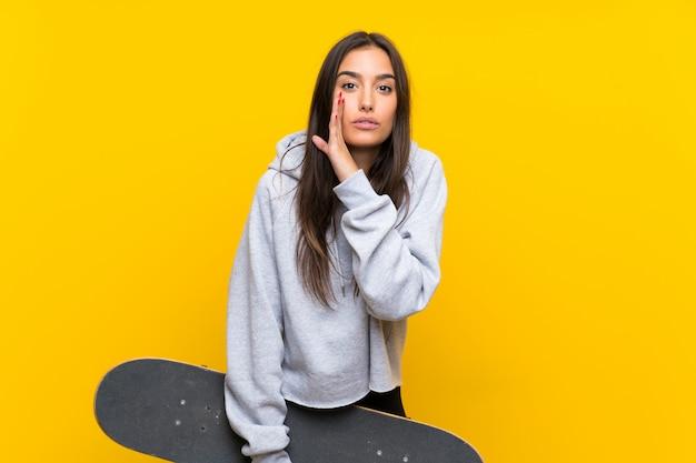 Młoda łyżwiarka kobieta nad odosobnioną kolor żółty ścianą szepcze coś Premium Zdjęcia