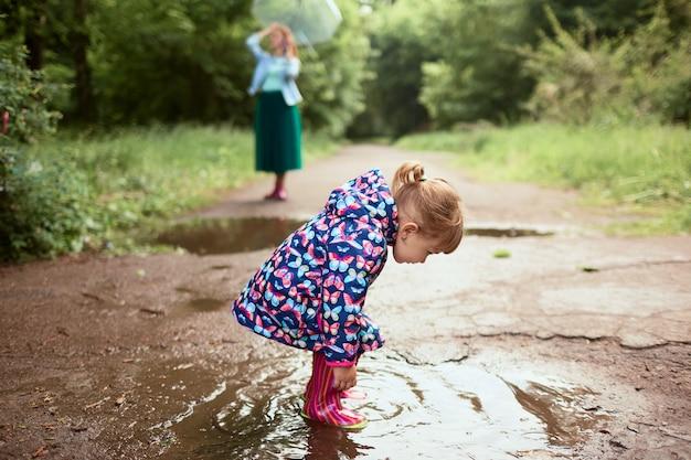 Młoda Mama I Mała Córka Bawią Się Spacery W Gumboots Na Baseny W Parku Darmowe Zdjęcia