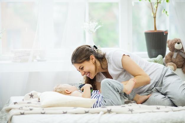 Młoda matka całuje swoje dziecko leżące na łóżku Premium Zdjęcia