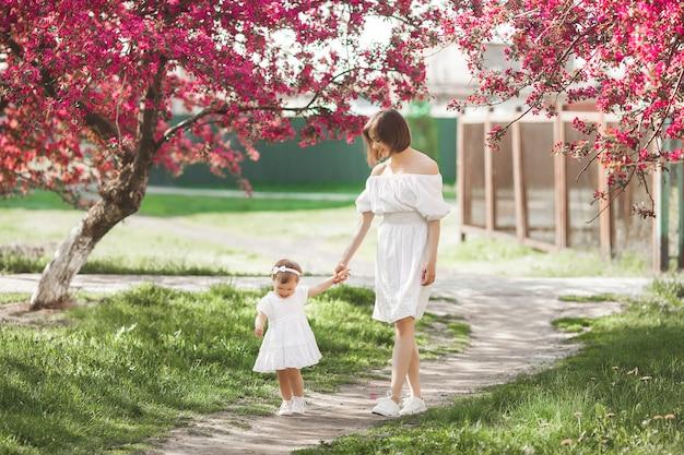 Młoda Matka I Jej Córeczka Spacery W Parku Razem W Okresie Wiosennym. Szczęśliwa Rodzina Na Zewnątrz. Kochać Z Uroczą Córeczką. Premium Zdjęcia