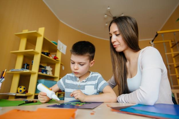 Młoda Matka Odrabia Lekcje Z Synem W Domu. Rodzice I Szkolenie Premium Zdjęcia