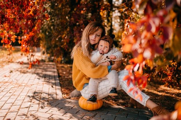 Młoda Matka Siedzi Z Dzieckiem W Parku Jesienią Premium Zdjęcia