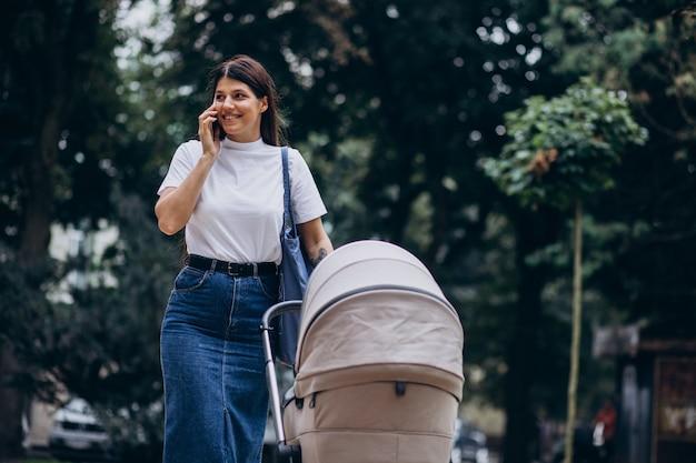 Młoda Matka Spaceru W Parku Z Wózkiem Dziecięcym I Rozmawia Przez Telefon Darmowe Zdjęcia