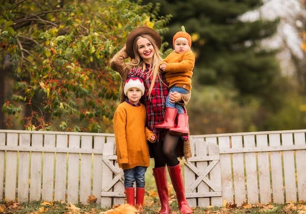 Młoda Matka W Brązowym Swetrze Przytula Syna I Córkę W Jesiennym Parku Premium Zdjęcia