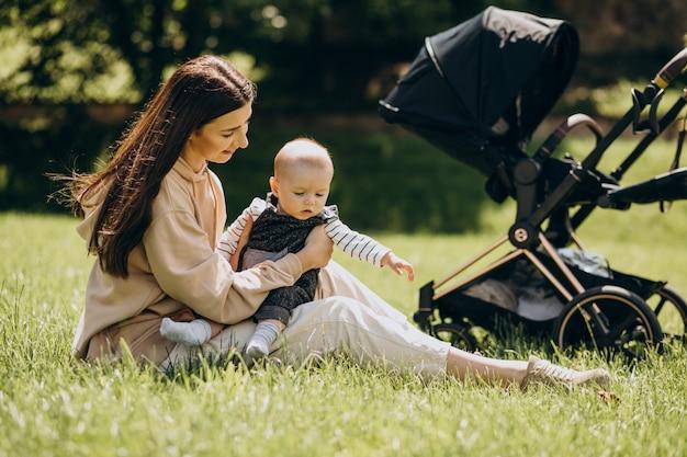 Młoda Matka W Parku Z Dzieckiem Siedzi Na Trawie Darmowe Zdjęcia