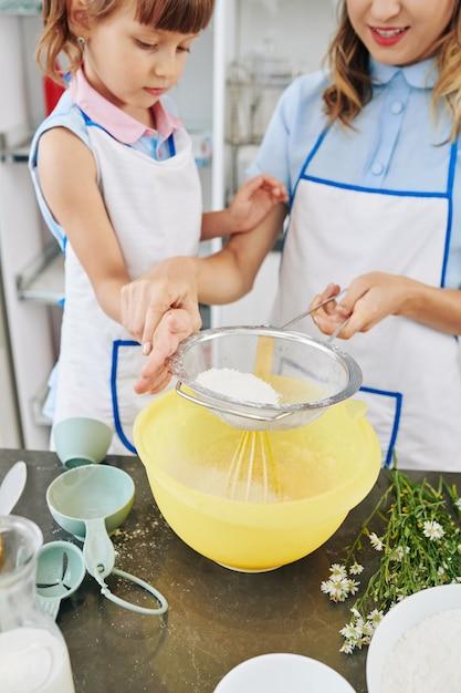Młoda Matka Wyjaśnia Córce, Jak Przesiać Mąkę Do Dużej Miski Podczas Robienia Ciasta Naleśnikowego Premium Zdjęcia