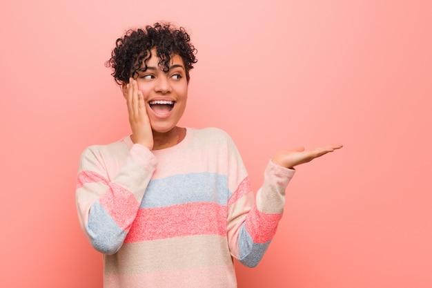 Młoda mieszana amerykanin afrykańskiego pochodzenia nastolatka kobieta trzyma kopię na dłoni, trzymał rękę nad policzkiem. zaskoczony i zachwycony. Premium Zdjęcia