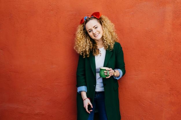 Młoda modna kaukaska kobieta z kędzierzawym włosy jest ubranym pałąk i stylową kurtkę. Premium Zdjęcia