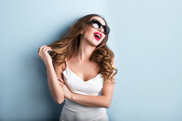 Młoda Modna Kobieta Na Błękitnym Tle. Emocje. Premium Zdjęcia